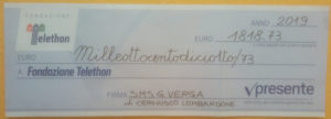 L'assegno con il contributo alla fondazione Telethon